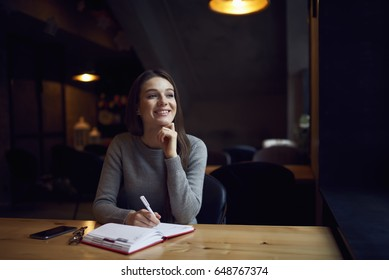 Charming attractive female author of articles enjoying working in coffee shop creating new texts writing in notebook,talented journalist analyzing information for research satisfied with occupation