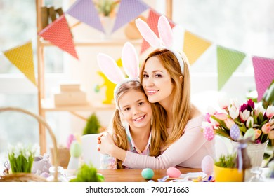 Charming, attractive, pretty, sweet mother and daughter preparing for Easter, hugging, smiling looking at camera, spending, enjoying time together, wearing bunny ears, costume