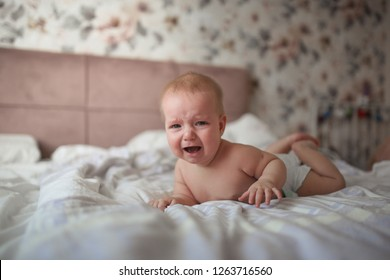 charming baby, 6 months old, lies crying on his stomach on a bed in a bright, real interior, a childhood end, and teeth are cut, colic of newborns.