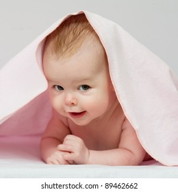Charming baby. Beautiful baby under pink blanket