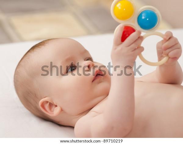 Agradable bebé. Bebé jugando con el juguete tirado en la espalda