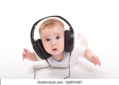 charming baby on a white background with headphones listening to music. Photo from the depth of focus and artistic blur