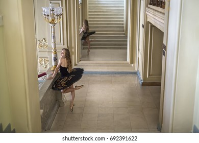 Charming ballerina in a black tutu with colorful rhinestones stands next to the stairway in the luxury interior. Her left leg is in the air. She reflected in the large mirror behind her. Horizontal.