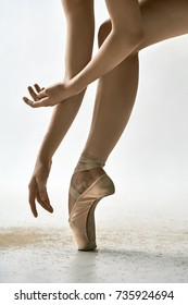 Charming ballerina is posing in the studio on the light background. She stands on the toe and holds her arms next to the leg. Girl wears beige pointe shoes. Closeup. Vertical.