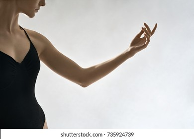 Charming ballerina is posing in the studio on the light background. She holds her left arm in the air. Girl wears a black leotard. Closeup. Horizontal.