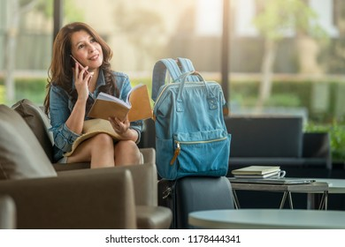 Charming beautiful business woman smile in casual style using smartphone and reading a book with laptop on table at airport terminal.