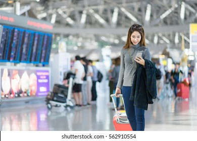 Charming beautiful business woman smile in casual style using smartphone with blur the airport terminal.