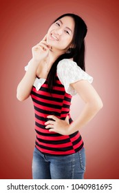 Charming beautiful chinese woman smiling over red background