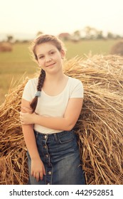 Charming beautiful girl blonde in straw fields at sunset and smiles. soft focus