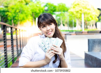 Charming beautiful girl hold a lot of dollars. Attractive asian woman is so young and can earn a lot of money. Gorgeous girl is thinking how to earn more money or how to investment. look at copy space