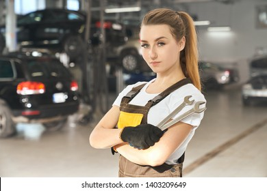 Charming, beautiful girl holding wrenches, looking at camera, posing. Pretty young woman working as mechanic in autoservice, wearing in white t shirt and coveralls.