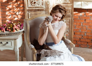 Charming and beautiful girl in white dress sitting on the couch on a background of a brick wall, smiling and holding his little kitten, in the interiors