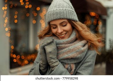 Charming beautiful happy woman with a magic smile in a trendy gray coat and a knitted fashionable hat with a scarf on the street near the yellow lights on holiday
