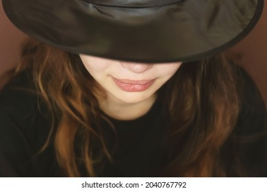 A charming, beautiful, sensual young girl on a dark background with a hat covering half of her face. A dramatic portrait of a young woman in a black wide-brimmed hat. Hidden eyes.  Selective focus