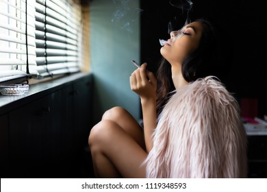 Charming beautiful sexy woman is smoking marijuana or cigarette. Attractive beautiful girl feel relaxing and happiness. She feel absent minded or in a dreamy state. Beautiful asian woman wear fur coat