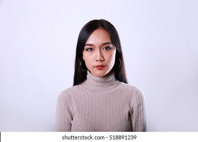 Charming beautiful tan skin Asian woman serious face looking with dramatic feeling. Presenting your product.