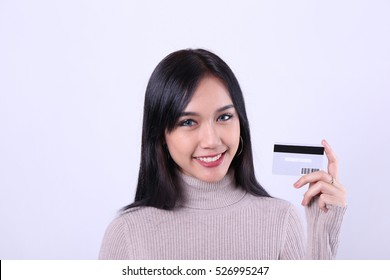 Charming beautiful tan skin Asian confident woman holds shopping bags and credit card. Presenting your product. Shopping online.