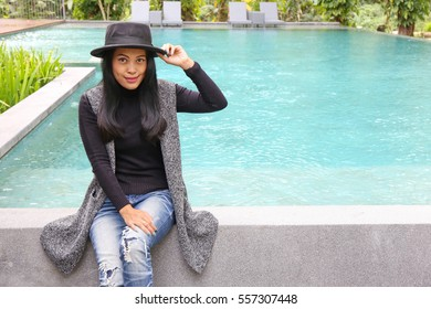 Charming beautiful tan skin Asian woman sit on deck and use phone at swimming pool. Presenting your product with good looking chic business woman.