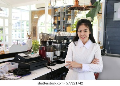 Charming beautiful tan skin Asian chic woman barista standing on coffee shop counter and coffee machine. Business owner people concept.