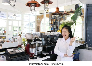 Charming beautiful tan skin Asian chic woman barista standing on coffee shop counter and coffee machine. Business owner people smiling concept.