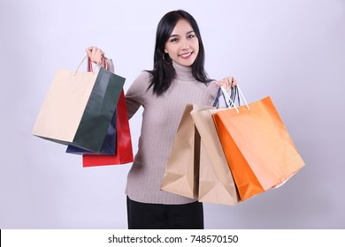 Charming beautiful tan skin Asian confident woman show shopping bags. Presenting your product. Shopping online shopaholic like weight lifting. Surprise discount price grand sale at new year festival.
