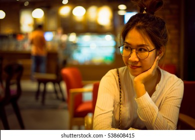 Charming beautiful woman in casual sitting and looking in coffee cafe shop with tungsten light.