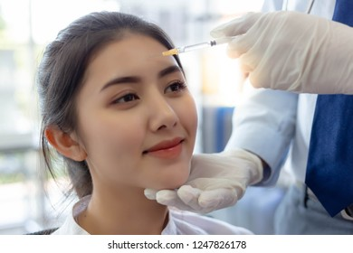 Charming beautiful woman or customer girl get satisfied and happy with quality of face lift at clinic of surgery when doctor inject Botulinum toxin A on forehead for reducing forehead line with smile