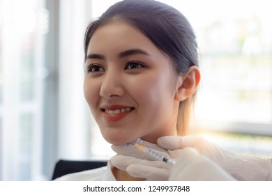 Charming beautiful woman or customer girl get satisfied and happy with quality of face lift at clinic of surgery when doctor inject Botulinum toxin A on chin for good shape at clinic room with smile