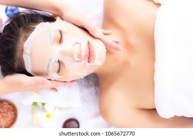 Charming beautiful woman feel relaxed. Attractive beautiful girl love aromatherapy massage. Gorgeous lady come to spa shop. Massager massage face and use collagen mask put on her face for rejuvenation