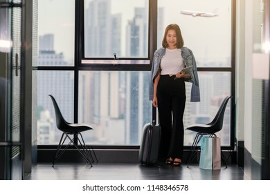 Charming beautiful woman go to foreign country for working. Attractive girl holding tablet. Pretty asia woman feel happy because she get good job, good salary. She arrives to airport early morning