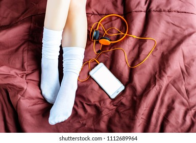 Charming beautiful woman is lying down on a bed with her smartphone or mobile phone, headphone. Attractive woman wears long white socks in the winter time at bedroom with white, isolated screen phone