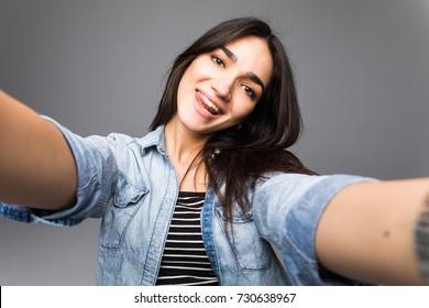 Charming beautiful woman take selfie from hands on grey