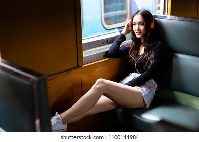 Charming beautiful woman is traveling on retro train and listening nice music during gorgeous woman is going back home. She puts her legs on chair and feels comfortable and relaxed. train background