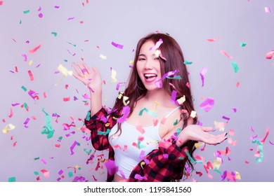 Charming beautiful young woman gets cheerful and happiness with smile and dance. Attractive beautiful women is celebrating some party, festival, new year or carnival with fireworks rainbow colors