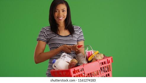 Charming black female holding grocery basket posing on green screen