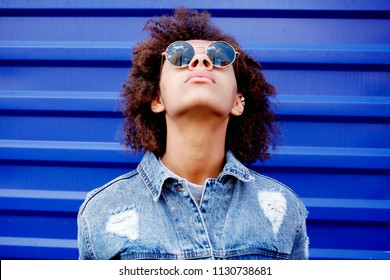 Charming black girl in a denim jacket, and round sunglasses with a curly Afro hair is standing outdoor, autumn day, fall fashion