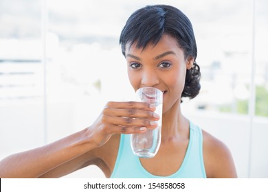 Charming black haired woman drinking a glass of water in a living room