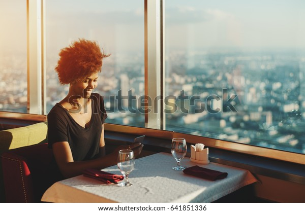 Charming black teenage girl with curly afro hair sitting in modern restaurant on the top of very high skyscraper near window with cityscape view, having online chat with her sister using smart phone