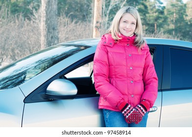 Charming blond woman standing by her car outdoors in winter forest