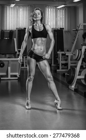 Charming blonde with elegant shape and perfect body posing in the gym.
