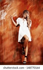 Charming blonde girl in romantic white dress over vivid background.