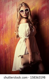 Charming blonde girl in romantic white dress and sunglasses over vivid background.