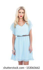 Charming blonde model in blue dress looking at camera on white background