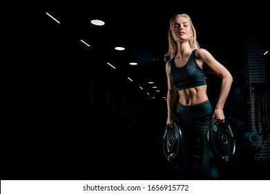 Charming blonde posing in the gym with dumbbells in her hands. Front view. The concept of sports, bodybuilding, fitness. Mixed media
