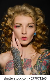 Charming blonde with a tattoo on body, dark background