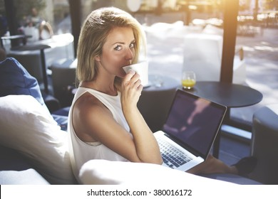 Charming blonde woman drinking cappuccino and looking at camera while sitting with laptop computer in co-working cafe, lovely hipster girl enjoying coffee while waiting downloading a file on net-book