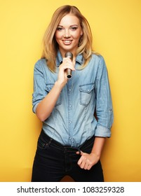 charming blonde woman singing with microphone in studio over yellow background
