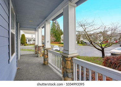 Charming blue home exterior with a nice covered porch with columns and stone details. View of the territorial area from the porch.