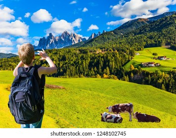 Charming boy with a large backpack photographs farm cows with a mobile phone. Delightful mountain valley in the Dolomites.  The concept of ecological and photo tourism
