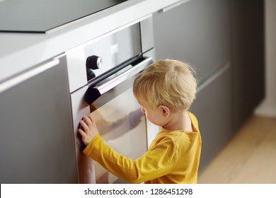 Charming boy waiting preparing food in domestic kitchen. Little mom's helper looks into oven and waiting cooking apple pie.